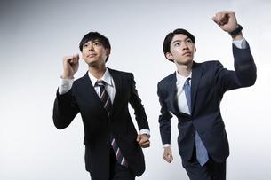 走り出すスーツ姿の20代男性2人のポートレートの写真素材 [FYI03391657]