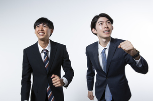 走り出すスーツ姿の20代男性2人のポートレートの写真素材 [FYI03391659]