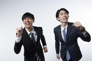 走り出すスーツ姿の20代男性2人のポートレートの写真素材 [FYI03391662]