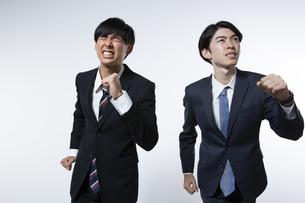 走り出すスーツ姿の20代男性2人のポートレートの写真素材 [FYI03391663]