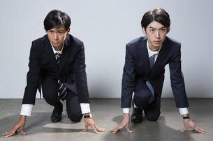 走り出すスーツ姿の20代男性2人のポートレートの写真素材 [FYI03391669]