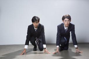 走り出すスーツ姿の20代男性2人のポートレートの写真素材 [FYI03391671]