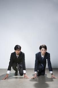 走り出すスーツ姿の20代男性2人のポートレートの写真素材 [FYI03391672]