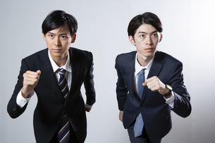 走り出すスーツ姿の20代男性2人のポートレートの写真素材 [FYI03391674]