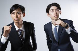 走り出すスーツ姿の20代男性2人のポートレートの写真素材 [FYI03391675]