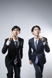 走り出すスーツ姿の20代男性2人のポートレートの写真素材 [FYI03391677]