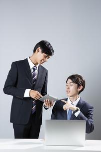 タブレットを見せ説明をするスーツ姿の男性2人の写真素材 [FYI03391731]