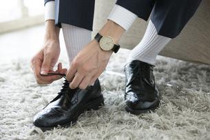 革靴の紐を結ぶ男性の足元の写真素材 [FYI03391769]