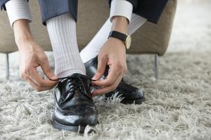 革靴の紐を結ぶ男性の足元の写真素材 [FYI03391771]