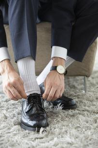 革靴の紐を結ぶ男性の足元の写真素材 [FYI03391773]