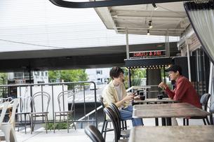 カフェで話す20代男性2人の写真素材 [FYI03391783]