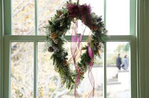 窓に飾られたフラワーリースの写真素材 [FYI03391951]