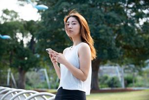 公園でスマホを持っている女性の写真素材 [FYI03392072]