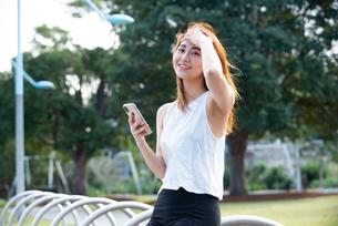 公園でスマホを持って笑っている女性の写真素材 [FYI03392077]