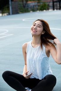 公園でスマホを持って笑っている女性の写真素材 [FYI03392089]