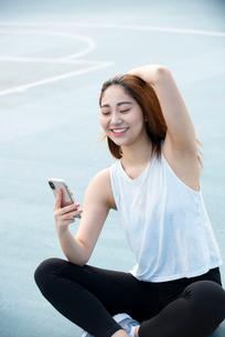 公園でスマホを見て笑っている女性の写真素材 [FYI03392776]