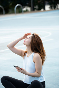 公園でスマホを持っている女性の写真素材 [FYI03392779]