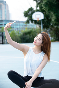 スマホでセルフィーをしている女性の写真素材 [FYI03392794]