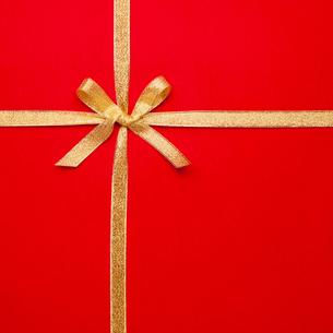 赤い背景にゴールドのリーボンで蝶々結びの写真素材 [FYI03394306]