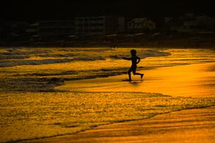 夕暮れの波打ち際で遊ぶ子供の写真素材 [FYI03394601]