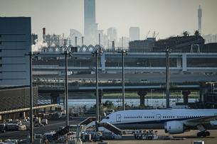 飛行機と街並みのシルエット(羽田空港)の写真素材 [FYI03394653]