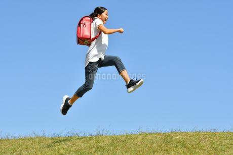 青空でジャンプする女の子(ランドセル)の写真素材 [FYI03395543]
