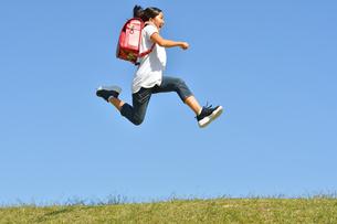 青空でジャンプする女の子(ランドセル)の写真素材 [FYI03395544]