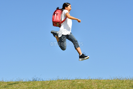 青空でジャンプする女の子(ランドセル)の写真素材 [FYI03395545]