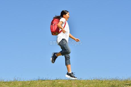 青空でジャンプする女の子(ランドセル)の写真素材 [FYI03395546]