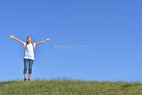 青空でバンザイする小学生の女の子(ランドセル)の写真素材 [FYI03396322]