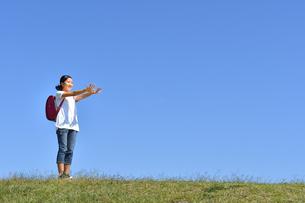 青空でポーズをきめる小学生の女の子(ランドセル)の写真素材 [FYI03396323]
