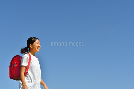 青空で笑う小学生の女の子(ランドセル)の写真素材 [FYI03396677]