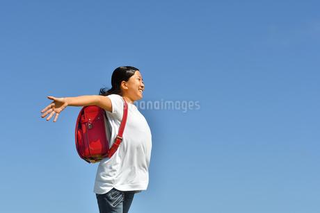 青空で手を広げる小学生の女の子(ランドセル)の写真素材 [FYI03396678]