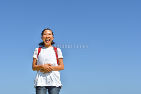 青空で笑う小学生の女の子(ランドセル)の写真素材 [FYI03396679]