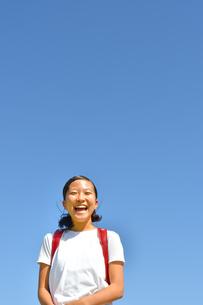青空で笑う小学生の女の子(ランドセル)の写真素材 [FYI03396680]