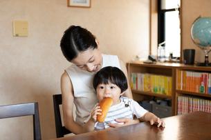 母親の膝の上でパンを食べる子どもの写真素材 [FYI03396801]