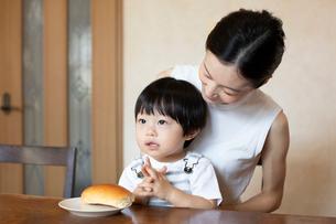 母親の膝の上でパンを食べる子どもの写真素材 [FYI03396802]