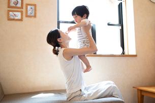 リビングルームで子どもを抱き上げる母親の写真素材 [FYI03396820]