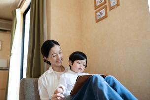 子どもを膝の上に乗せてソファーに座る母親の写真素材 [FYI03396827]