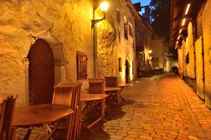 カタリーナの小路の通路脇にある店舗のレストランのイスとテーブル・旧市街は世界遺産(右の壁には聖カタリーナ教会の14~15世紀に収められていた墓石が並べられている)・旧市街は世界遺産の写真素材 [FYI03397084]