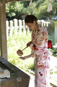 手水舎で手を清める浴衣の女性の写真素材 [FYI03397513]