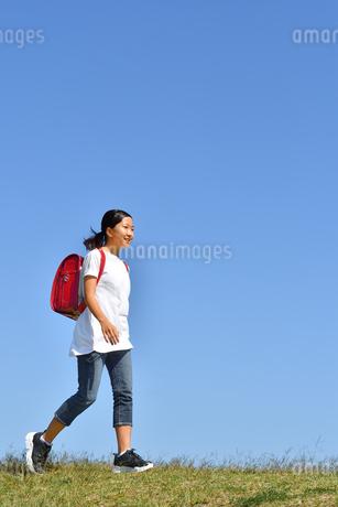 青空で歩く小学生の女の子(ランドセル)の写真素材 [FYI03397597]