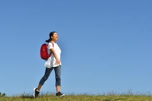 青空で歩く小学生の女の子(ランドセル)の写真素材 [FYI03397599]