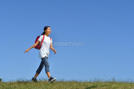 青空で歩く小学生の女の子(ランドセル)の写真素材 [FYI03397600]