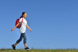 青空で歩く小学生の女の子(ランドセル)の写真素材 [FYI03397601]