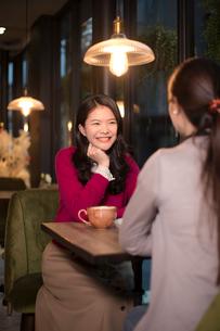 コーヒーショップで友人と話す若い女性の写真素材 [FYI03397864]