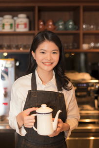 コーヒーポットを持つ若い女性の写真素材 [FYI03397878]