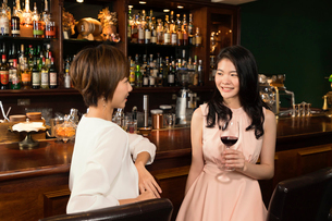 カウンターでワインを飲む若い女性の写真素材 [FYI03397931]