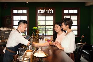 バーで飲む若い女性と店員の写真素材 [FYI03397950]