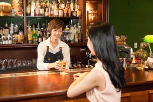 グラスを差し出す店員と女性客の写真素材 [FYI03397985]
